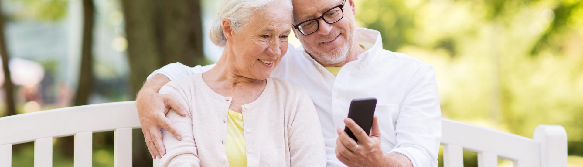 Zwei ältere Menschen gucken auf ein Handy